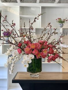 This incredible centerpieces created with coral peonies, cherry blossoms, and phalenopsis orchids...Spring is in the air.
