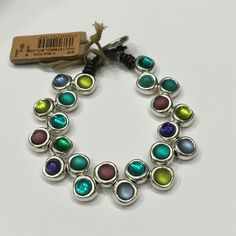 Uno de 50 bracelet. Original and colourful leather bracelet in which have been interlaced alternately, in a zig zag way, silver plated metal parts with embedded Murano glasses in red, blue, green and lime. The lock is a flat silver plated metal piece that contrasts to a ground-breaking point with the leather. Jewelry Bracelets