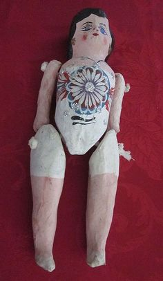 "This little lady stands 13 1/2"" tall,has short, black hair, and is wearing white swimsuit/undies. She is crudely made, with hand painted flower decoration, including glitter, on her chest. Her arms, and legs are attached to the body with a piece(two pieces) of knotted rope. Charming, and naive"
