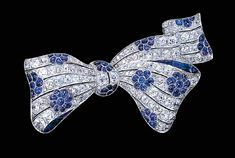 A FINE SAPPHIRE AND DIAMOND BOW BROOCH   Designed as diamond openwork lines with cabochon-cut sapphire flowerheads set at intervals to the french-cut sapphire edge detail, circa 1924