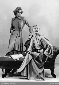 Två modeller vid en divan. Modellen längst bak bär klänning och den sittande modellen bär morgonrock och tofflor, cigarett och cigarettmunstycke i handen. Fotograf: Sten Didrik Bellander, ca 1950-1955