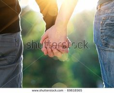 Concept shoot of friendship and love of man and woman: two hands over sun ray and nature by Aleksandr Markin, via ShutterStock