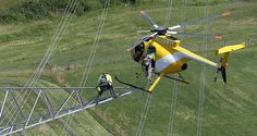 FirstEnergy linemen board a Hughes MD500 helicopter from the open-arm of a transmission tower after installing the new 345 kilovolt transmission line. (John Kuntz / The Plain Dealer)
