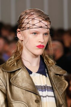 Hair was styled by Eugene Souleiman and adorned with accessories including feathers, netting and gold glitter paint.