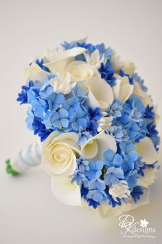 """http://dkdesignshawaii.blogspot.com/2011/01/something-bluebouquet-boutonniere.html  Note: """"The bouquet consists of champagne ivory roses, ivory callas, ivory tulips, tuberose, with light blue hydrangeas, as well as light and dark blue hyacinth. There is absolutely no greenery filler in this bouquet!""""  Clay flowers!"""