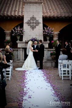 Courtyard ceremony with purple rose petals lining the aisle   Lasting Images Photography   villasiena.cc