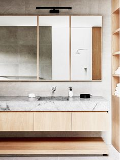 Warm minimalist bathroom with a light wood vanity with a marble top, light wooden mirrors, and a mounted black sconce