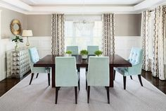 Lovely aqua blue and gray dining room is furnished with a dark brown dining table surrounded by aqua blue dining chairs placed on a gray diamond pattern rug and lit by a lucite chandelier hung rom a tray ceiling.