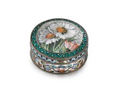 A silver and enamel pictorial box, 20th Artel, Moscow, 1908-1917 circular, the hinged lid painted en plein with daisies within a border of beaded scrolls on a green-enamelled ground, the sides with shaded cloisonné flowers below a stylised wave border, 88 standard diameter: 5.8cm, 2 1/4 in.