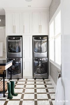Pull Out Cabinets Between Stacked Washers and Dryers. This laundry room is equipped with two sets of stacked Maytag washers and dryers placed on gray and white marble floor tiles enclosed on either side of and beneath white cabinets adorning long brass pulls. An adjacent wall features windows dressed in white roman shades and framed with gray grasscloth wallpaper.   Designed by Alice Lane   Photographed by Nicole Gerulat