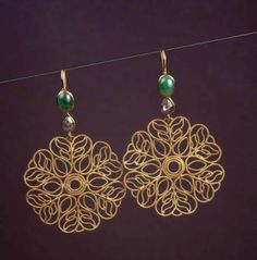 Decorative flower meticulously handcrafted in 22k gold filigree work is accented with a diamond and emerald