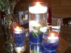 vase with pebbles and flowers in water with a lighted candle floating on top