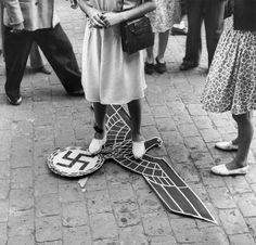 Tolosa, Francia, ore 18.03, 19 agosto 1944. Un'aquila nazista calpestata da una donna a Place Wilson. Lo stesso giorno in cui la città di Tolosa fu liberata, partigiani e cittadini tolsero tutti i simboli dell'occupazione dalle strade abbattendo i cartelli in tedesco usati dalle forze naziste.