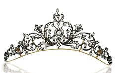 A LATE 19TH CENTURY DIAMOND TIARA / NECKLACE Of scrolling floral and foliate design, with central old brilliant-cut diamond cluster among a similarly-set graduated openwork panel, raised on a plain frame with detachable backchain, mounted in silver and gold, circa 1890