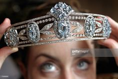 A model displays a tiara from Lady Hesketh's collection from circa 1910 and composed of a series of sky-blue oval aquamarines set among diamonds at a preview 08 May 2007 in Geneva. The tiara is expected to fetch 75,000 to 125,000 Swiss francs (USD 60,000 to 100,000) at a Sotheby's auction next 17 May.  AFP PHOTO / FABRICE COFFRINI (Photo credit should read FABRICE COFFRINI/AFP/Getty Images)