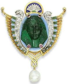 N EGYPTIAN REVIVAL EMERALD, ENAMEL AND DIAMOND BROOCH Of shield shape, centering upon an emerald cameo depicting a facing Ancient Egyptian head, surrounded by two diamond-set winged snakes applied with blue and green enamel, suspending a baroque-shaped pearl, late 19th Century, 5.8 x 4.6 cm.