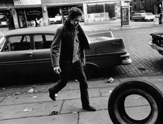 Bob Dylan in an urban scene. Whenever I think of hippie excesses, I need to be reminded of the big fins on American cars of the time and that wasteful concept of planned obsolescence. No wonder we rebelled.