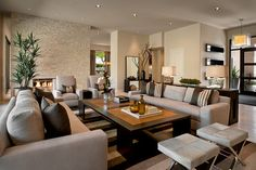This handsome living room is eye catching with its strong neutrals, and the designer also pulled off major challenges. The living room is just beyond the front door, so a long console table was placed behind the first sofa to create a sense of entry. The two facing sofas provide great symmetry, adding to the transitional feel of the room. Two chairs were placed in front of the fireplace, which is in the corner. The fireplace in this case acts as a backdrop rather than the focal point.