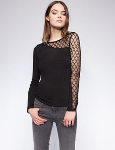 Chic black long sleeve top featuring a mesh panel on left shoulder front and back. Soft stretchy fabric. Cotton polyester blend. Model is wearing a size small.