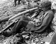 Two American soldiers rest against a chalk cliff on the beach of the Normandy coast of France after landing in June,1944. Man at right is wrapped in blanket & soldier at left stretches out beside an inflatable belt he apparently wore while making his way ashore.