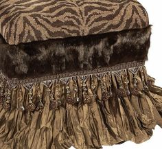 The Zanzibar Foot Stool is covered is a tiger chenille and skirted with a light bronze crushed silk. The faux mink detailing along with the over-sized beads finish it off perfectly!