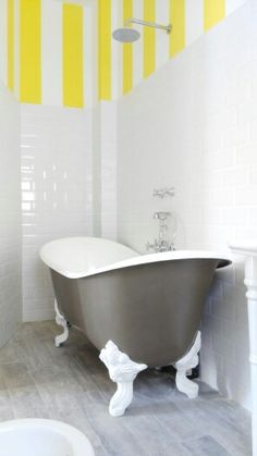 #bagno principale con #vasca a libera installazione con zampe di leone. #rivestimento stile #inglese e #pittura a fasce verticali gialle e bianche. #pavimento in #GresPorcellanato effetto #legno