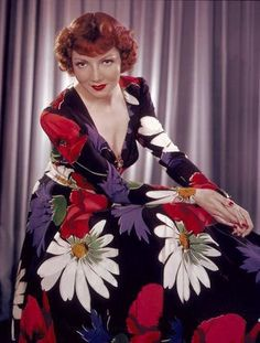 A vibrantly beautiful colour photo of actress Claudette Colbert, c. 1943 vintage fashion style icon bold floral dress red white purple black graphic print 40s icon color