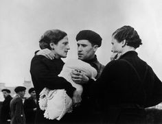 Robert Capa • Spain, Barcelona. January 13, 1939. Man with two women and a baby preparing for mobilization as General Franco's troops approached the City