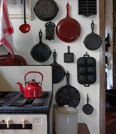 Panelas de ferro fundido e esmaltadas enfeitam a parede da cozinha, dando-lhe um toque pessoal.  Fotografia: Jonny Valiant.
