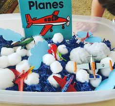 Tot School....In the Sky Unit. Airplane Sensory Bin. We kept this sensory bin as a easy clean up using shredded paper, cotton balls, pom poms & toy airplanes.  Little Guy loved finding the airplanes. I also gave him measuring cups & he had fun transferring cotton balls from one to the other.