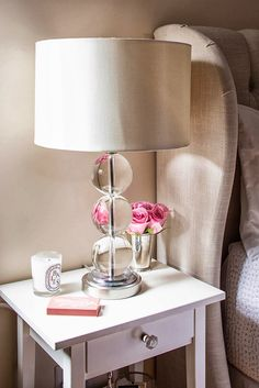 Natural linen tufted headboard, white IKEA Hemnes dresser with Anthropologie small Bauble Knob, Pier 1 acrylic stacked ball lamp, Diptyque Baies candle, mint julep cup with pink roses, and cute coral and white box of matches - adore!