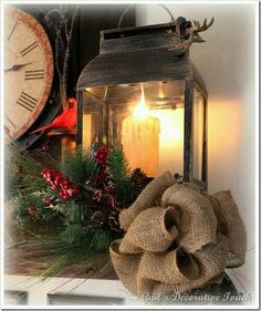 Mantel decor - Lanterns with an electric candle inside each one. Make a Christmas swag with a burlap bow to place in front of the lanterns. Birds, pinecones, faux Christmas greens and berries are added to finish the vignette. Christmas Lanterns, Christmas Swags, Burlap Christmas, Noel Christmas, Primitive Christmas, Country Christmas, Christmas Projects, Winter Christmas, Christmas Vignette