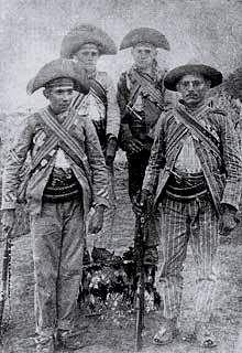 Uma das primeiras fotografias do bando de Lampião (primeira a esquerda). Nessa fotografia de 1921 ou 1922 está ainda o seu irmão, Antônio Ferreira (último à direita), o outro irmão, Levino Ferreira (terceiro) e o irmão de criação e amigo, Antônio Rosa Ventura (segundo).