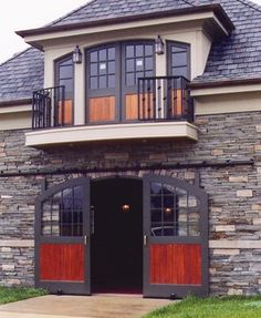 Love the stone facade and the wood in the doors. Barn doors by Lucas Equine. Do a guest house over the garage and a man cave under it. Have the garage designed so it can become an additional guest space for entertaining.