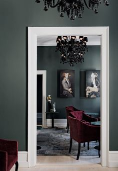 Elegant living room space in Baroque style with black chandeliers, dark walls and velvet armchairs.