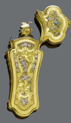 Enamel & Gold Perfume Flacon ca. 1760 w Allegoric Representation of Venus/Fortuna Sitting on Shell Decorated w Cherubs, a Parrot & Pelican, and Band, Volute, Tendril & Shell Motifs Flowers and Birds w  Fine Polychrome Enamel Pusher Decorated with a Diamond. Small Rock Crystal Flacon w Lozenge Decor Neck w Enameled Flower Ornaments Stopper w a Plastically Shaped Enameled Bird.