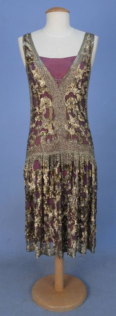 ADAIR PARIS BEADED TULLE OVERDRESS, 1920's. Sleeveless purple tulle with deep V-neck and back decorated with crystal bugle beads at neck, sides, waist and hem and allover abstract pattern of shaped metallic sequins and beads, dropped waist, skirt gathered in front, side slits. Labeled.