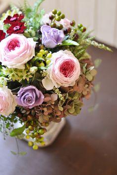 ピンクから白へのグラデーションは、咲き進むバラの自然な開花状態のようなローズメリアになっています。 コロンと丸いフォルムの可愛いらしいオールドローズにビターカラーのジニアを合わせ、アートグリーンをアレンジしてナチュラルテイストに仕上げた大人シックなアレンジメントです。広い空間にも飾っていただける大きなサイズですので、特別な贈り物に最適です。