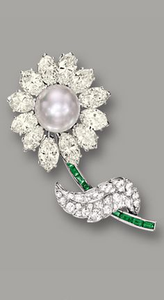CARTIER CULTURED PEARL, DIAMOND AND EMERALD 'FLOWER' BROOCH, CARTIER Modelled as a flower centring on a cultured pearl measuring approximately 12.00mm, the petals set with marquise-shaped diamonds of light yellow hue, the leaf set with brilliant-cut diamonds, the stem set with calibré-cut emeralds, the diamonds together weighing approximately 10.50 carats, mounted in platinum, signed.