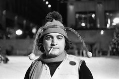 1975, Manhattan, New York, New York, USA — Comedian John Belushi, in a bumble bee costume, skates at the Rockefeller Center Ice Rink for a skit on Saturday Night Live.