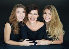 Stunning mother with two teenager daughters with long hair in Studio on black background and leaning on sofa  shot in natural daylight in studio.