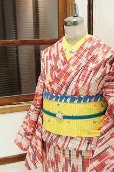 生成り色をベースに、赤と黒を基調にした矢羽根模様が浮かび上がるウールの単着物です。