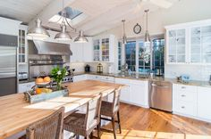 Contemporary Kitchen with High ceiling, L-shaped, Flat panel cabinets, Wood counters, Skylight, Hardwood floors, Glass panel