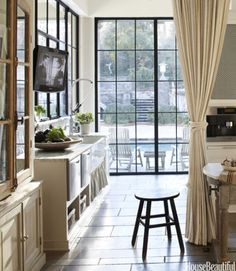 """In the kitchen of the same Atlanta house, a linen curtain runs on a track spanning the room and can be pulled """"to conceal the mess of preparation,"""" Webb says. Steel-and-glass casements frame views of the pool and garden. KWC Gastro faucet."""