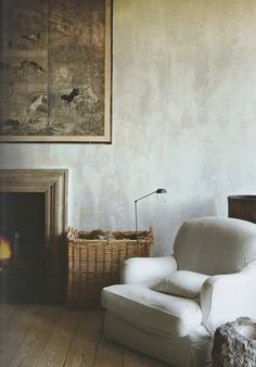 Rendered wall, stone fireplace surround, reclaimed timber floor, Axel Vervoordt
