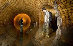 Two people explore the storm drain that was once the Fleet River, a tributary of the Thames in London
