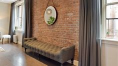 This sophisticated Brooklyn living room features a taupe tufted bench seat positioned in front of an exposed brick wall. Two windows on either side of the wall invite natural light into the space and are framed with soft gray curtains.