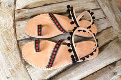 Greek leather sandals embellished with black woven trim with red flowers and black pom pom trim