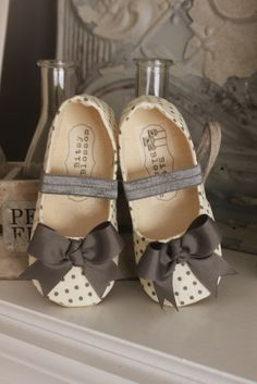 Bitsy Blossom loves to work with polka dots....it makes us happy! Our Giselle shoe is made with an ivory and grey polka dot fabric and a delicate grey bow at the toe. A coordinating grey elastic strap has also been added. Bitsy Blossom's toddler shoes are all handmade and created with great care and attention to detail. All of our shoes are made with modern and unique textiles. The insole is lightly padded for extra comfort. The soling material is waterproof, durable, abrasion r...