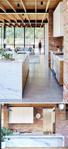In this modern kitchen, red brick, some of which was recycled from the garden paving, covers the wall and compliments the timber paneled cabinet doors and the Statuario marble used for the countertops and island.